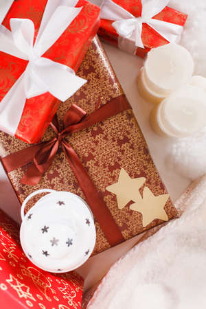 Christmas background with a red ornament, golden gift box, berries and fir in snow photo
