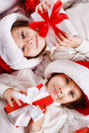 Santa hat Christmas girls holding christmas gifts smiling happy and excited  Cute beautiful santa children on red background  photo