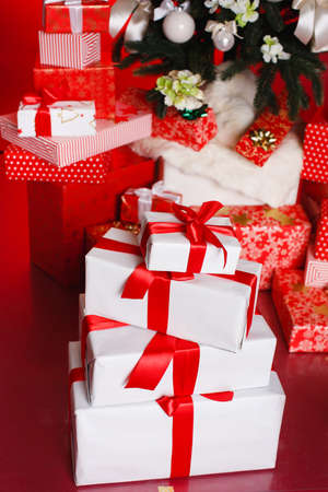 Beautiful gift boxes wrapped with ribbons and bow isolated on red background Stock Photo
