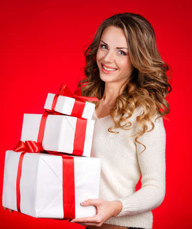 Woman wrapping Christmas presents  Christmas preparations concept with beautiful smile happy content young woman in her twenties with a red background  photo
