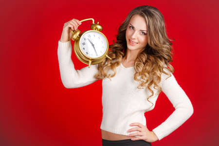 Pretty Woman In Santa Claus Costume Showing Clock Over Red Background photo