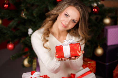 Beautiful woman near the Christmas tree with gifts, isolated on a dark  photo