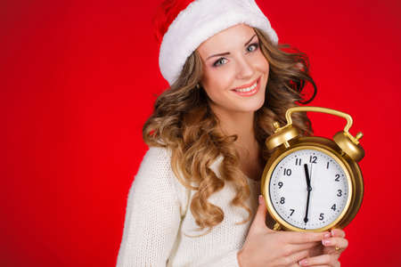 Pretty Woman In Santa Claus Costume Showing Clock Over Red  photo