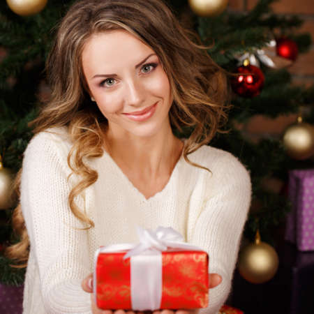 Beautiful woman with presents near the Christmas tree photo