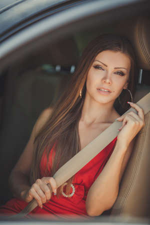 Portrait of beautiful sexy fashion woman model with bright makeup sitting in a car photo