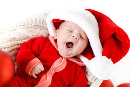 Adorable little baby wearing a santa claus suit and hat lying in straw basket photo