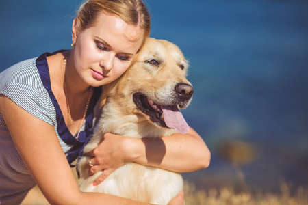 retreiver: Portrait of beautiful woman with her retreiver dog playing near blue sea