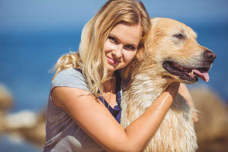 Portrait of beautiful woman with her retreiver dog playing near blue sea photo