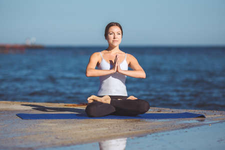 Healthy woman resting and curl up in fetal position outdoor at the sea  yoga pose  Series  photo