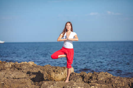 Beautiful positive blond girl clothing in white sit at the seaside on the rock and meditating in yoga pose Stock Photo