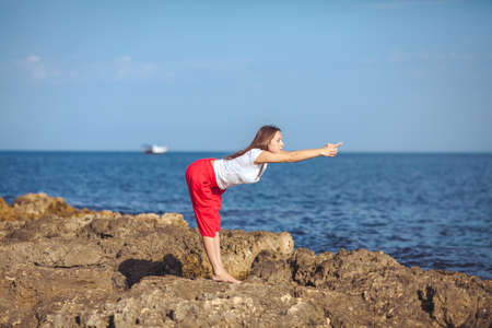 Beautiful positive blond girl clothing in white sit at the seaside on the rock and meditating in yoga pose photo