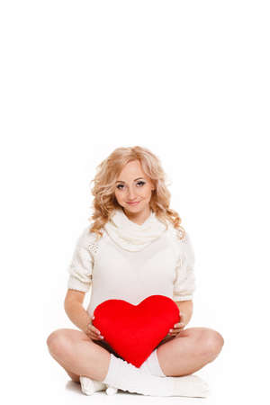Pregnant beautiful woman holding red heart pillow in her hands isolated on white background photo