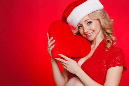 Portrait of beautiful pregnant woman in santa hat holding red heart in her hands on red background photo