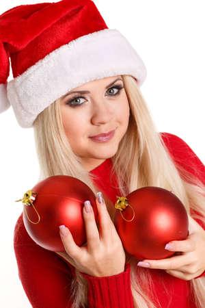 Ritratto di una bella donna che indossa un cappello di santa sorridente con palle rosse di Natale nelle sue mani photo