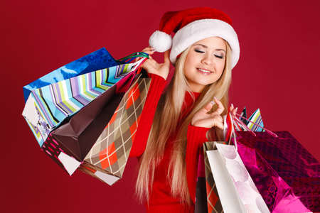 Woman shopping for christmas gifts  Young asian caucasian girl looking up smiling with shopping bags and santa hat  Copy space on the side  photo