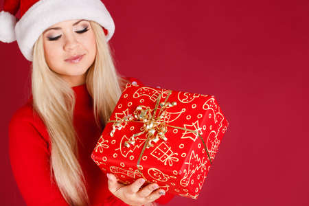 Santa woman showing gift wearing Santa hat  Christmas woman portrait of a cute, beautiful smiling mixed Asian   Caucasian model  Isolated on white background  photo