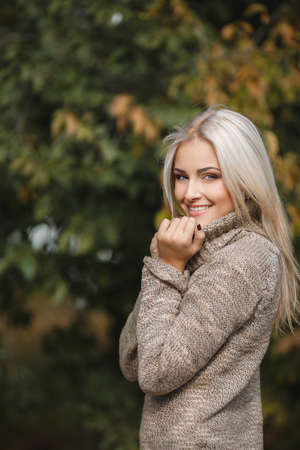 Portrait of beautiful young woman walking outdoors in autumn photo