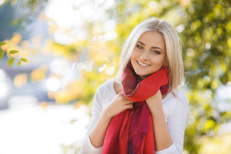 Close up portrait of young blonde beautiful woman in warm autumn scarf  Ourdoors  photo
