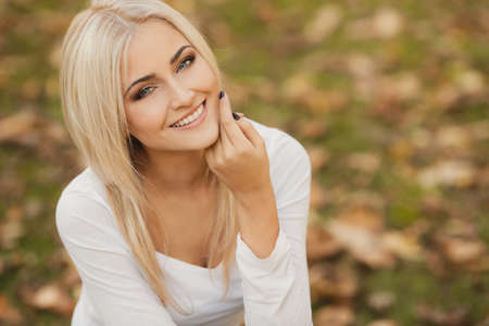 Close up portrait of young blonde beautiful woman in warm autumn scarf  Ourdoors  Stock Photo