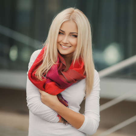 scarf: Portrait of young blonde beautiful woman in warm autumn scarf in the street  Ourdoors  Stock Photo