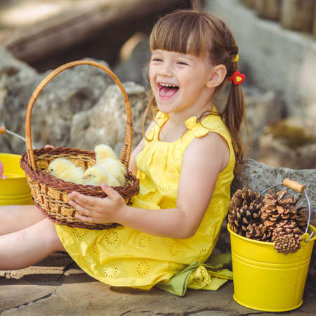 cute girl sitting in the village with her yellow chicken in the bucket photo