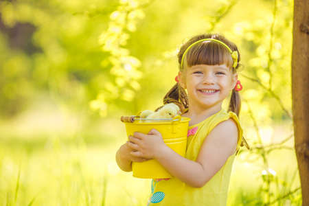 Happy little girl with a basket of small chickens sitting outdoor photo