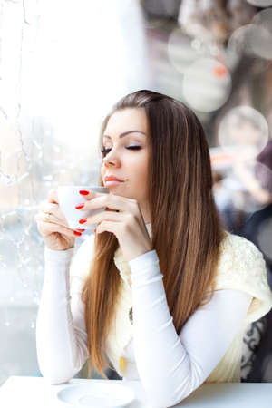 pretty young woman sitting in the cafe with a cup of coffee photo