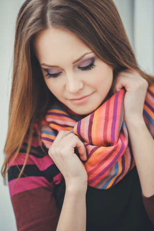 Portrait of beautiful young brunette woman in warm autumn scarf on the street  photo