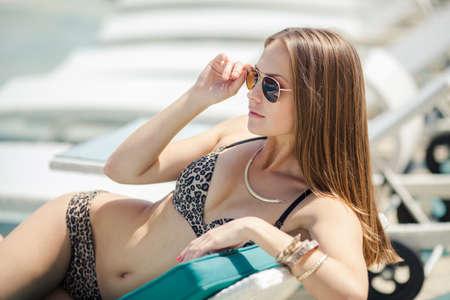 Beautiful woman resting near swimming pool on tropical resort photo