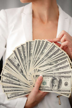 Portrait of a happy woman with a fan of american dollar currency notes photo