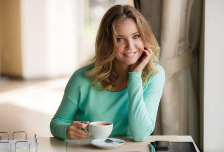 smiling woman: Portrait of a cute blonde smiling woman sitting in a cafe with a cap of coffee