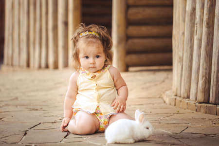 Little girl playing with rabbit in the village  Outdoor  Summer portrait  photo