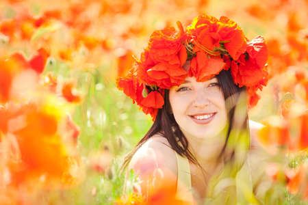 Beautiful woman in poppy wreath in summer poppy field  Outdoor portrait  photo