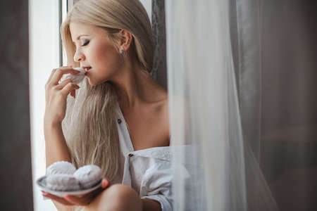 beautiful blonde woman: Closeup of a beautiful young woman sitting at a window of a house and holding a tray of marshmallows, happy life Stock Photo