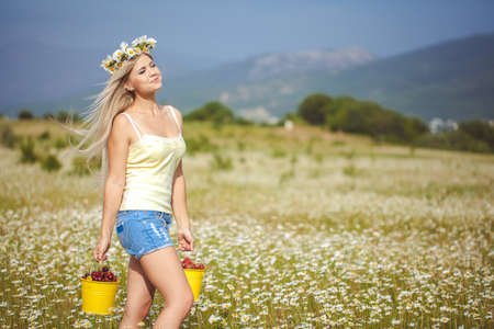 portrait of a beautiful Summer Woman in chamomile wreath in the field with two yellow buckets of strawberries and cherry  Outdoor  photo