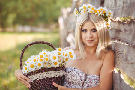 Attractive blonde in chamomile field  Young woman in wreath surrounded by chamomiles photo