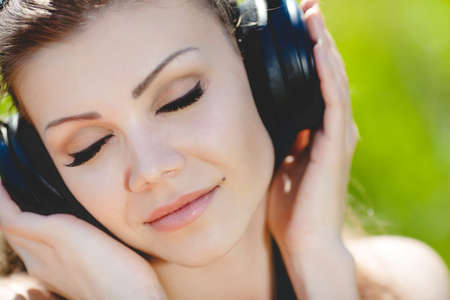 Close portrait of young beautiful smiling woman in headphones outdoors in summer photo
