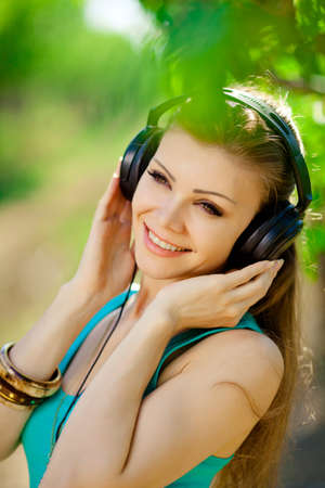 Beautiful young woman listen to music wearing headphones outdoor photo