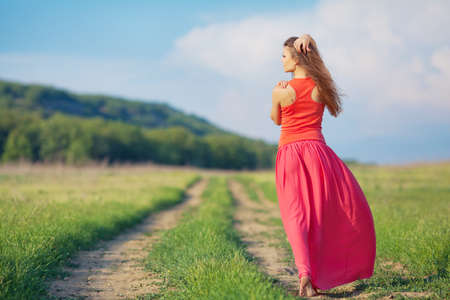 Portrait of barefoot woman in long red dress walking on the road in the green field in summer photo