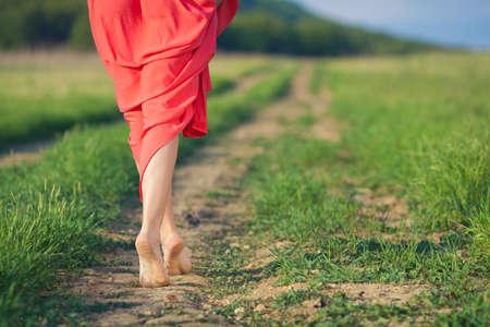 descalza: Retrato de mujer descalza en vestido largo rojo, caminando en la carretera en el campo verde en verano