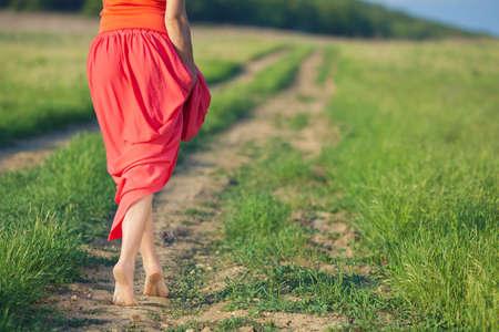 pies descalzos: Retrato de mujer descalza en vestido largo rojo, caminando en la carretera en el campo verde en verano