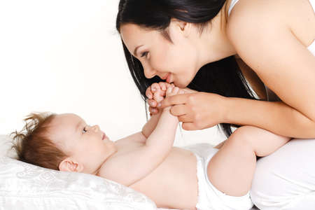 portrait of Happy cheerful family  Mother and baby kissing, laughing and hugging  Playful mood photo