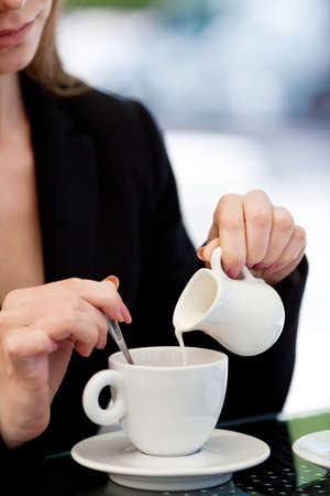 woman s hand pouring milk in white cup of coffee in outdoor cafe photo