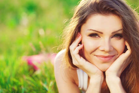 Close portrait of beautiful young woman on green grass in the summer outdoors Stock Photo