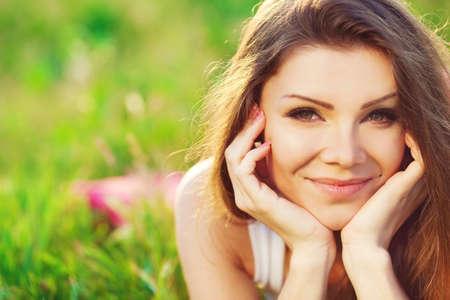 Dicht portret van mooie jonge vrouw op groen gras in de zomer buiten