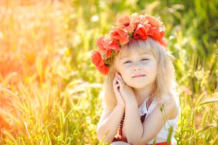 Cute child girl in poppy field photo