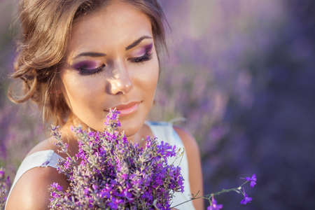 purple dress: Beautiful provence woman relaxing in lavender field watching on sunset holding basket with lavanda flowers  Series  alluring girl with purple lavender  blond lady in blossom field   Ukraine - Crimea Stock Photo