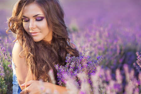 lavanda: Beautiful provence woman relaxing in lavender field watching on sunset holding basket with lavanda flowers  Series  alluring girl with purple lavender  blond lady in blossom field   Ukraine - Crimea Stock Photo