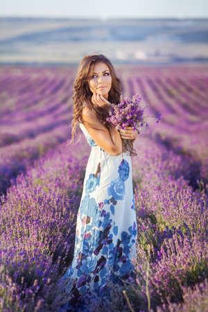 field and sky: Mujer hermosa que se relaja en Provence campo lila viendo la puesta de sol con canasta con flores de lavanda