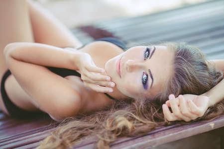 suntan: Portrait of woman sunbathing in bikini at tropical travel resort  Beautiful young woman lying on sun lounger  Summer  Outdoor